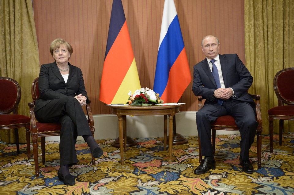 Photo - CORRECTS DATE  German Chancellor Angela Merkel, left, meets with Russian President Vladimir Putin in Deauville, France as they travelled to France ahead of the 70th anniversary of D-Day commemorations on Friday, June 6, 2014. (AP Photo/RIA Novosti, Alexei Nikolsky, Presidential Press Service)