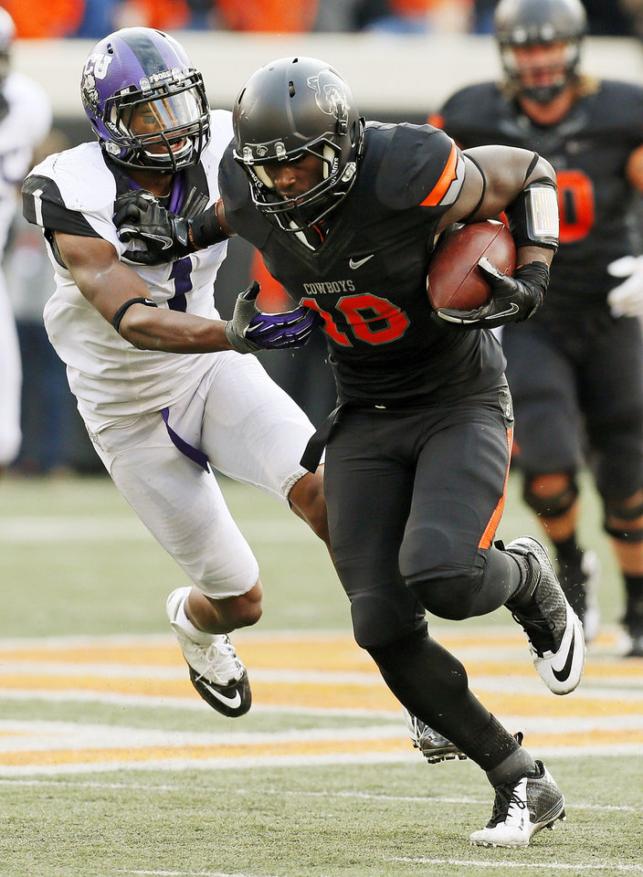 Photo - Oklahoma State's Blake Jackson (18) pushes away TCU's Chris Hackett (1) after a catch in the fourth quarter during a college football game between Oklahoma State University (OSU) and Texas Christian University (TCU) at Boone Pickens Stadium in Stillwater, Okla., Saturday, Oct. 27, 2012. OSU won, 36-14. Photo by Nate Billings, The Oklahoman