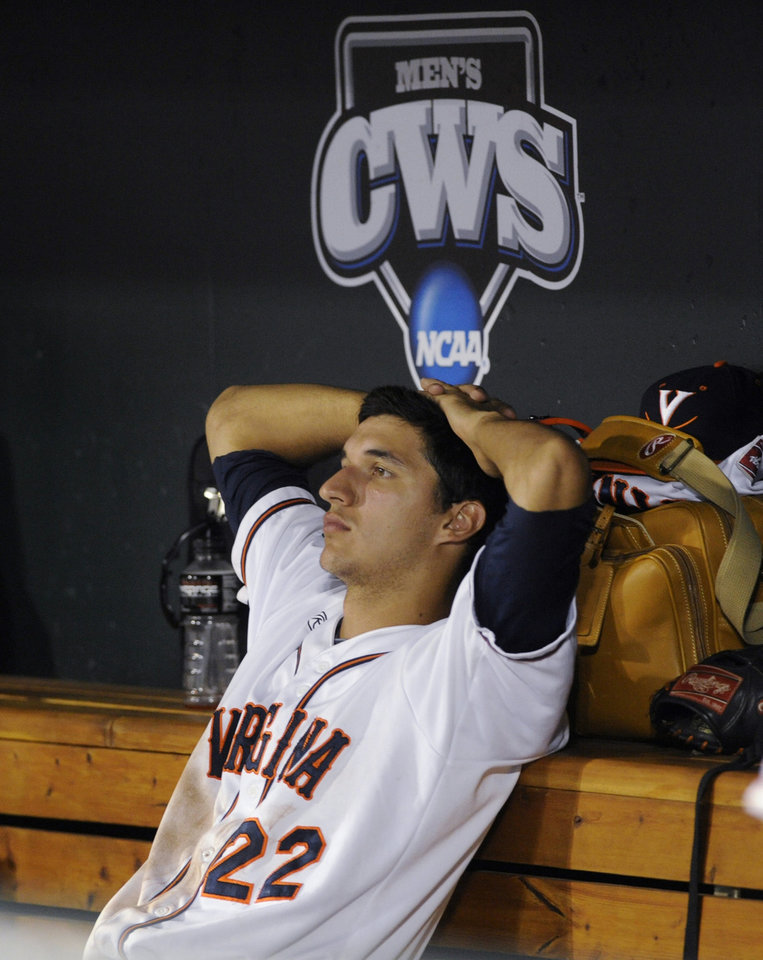 Photo - Virginia's Daniel Pinero watches as Vanderbilt players celebrate a 3-2 win in the deciding game of the best-of-three NCAA baseball College World Series finals in Omaha, Neb., Wednesday, June 25, 2014. (AP Photo/Eric Francis)