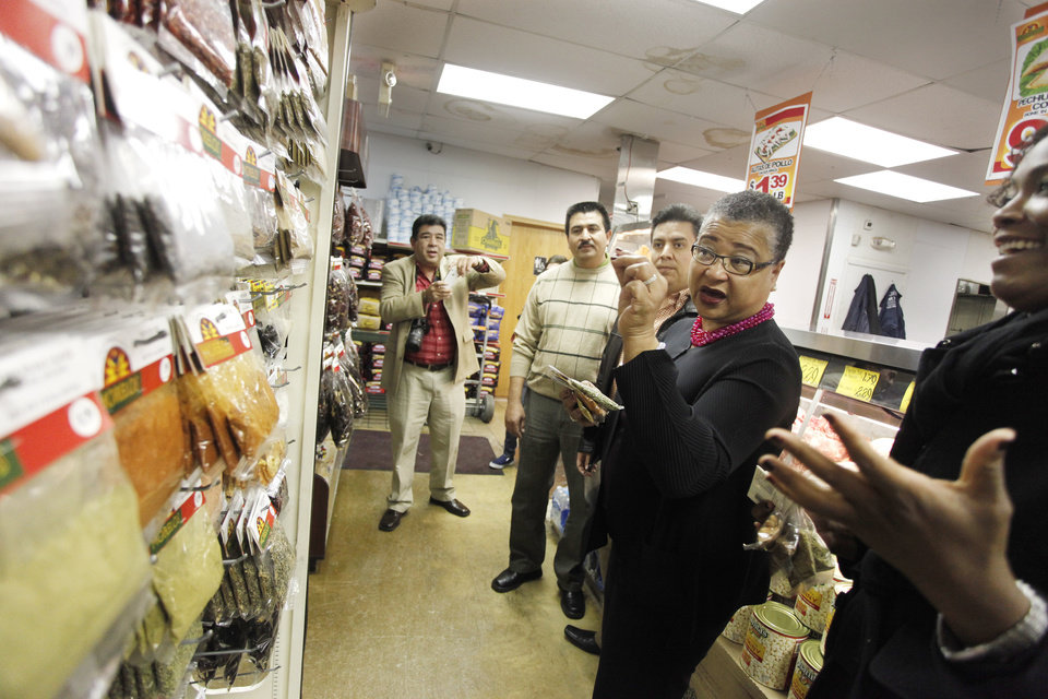 Photo - Francisco Ibarra, CEO, left, and Tulsa manager Manuel Gomez talk about spices with Small Business Administration Deputy Administrator Marie Johns while touring Supermercados Morelos in Oklahoma City, November 30, 2011. Photo by Doug Hoke, The Oklahoman