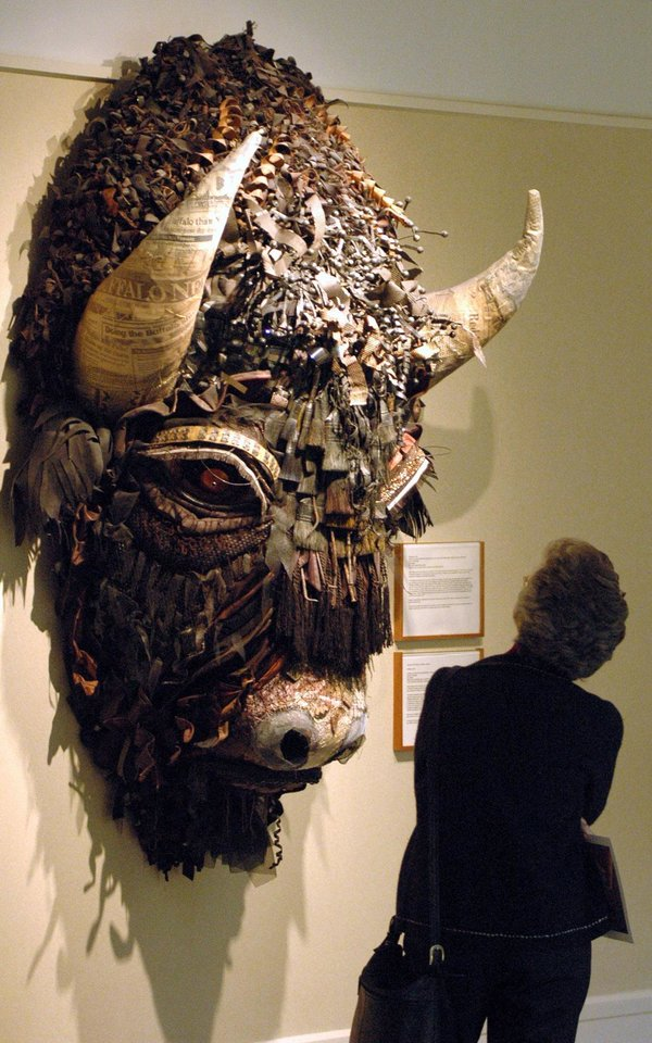Photo - FILE - This Jan. 27, 2006 file photo shows a woman looking at Buffalo, a mixed media piece by artist Holly Hughes, part of the Capitol Art Collection at the Capitol in Santa Fe, N.M. The collection was created in 1991 and consists of nearly 600 works exhibited in the building's public spaces and on the grounds outside. The collection is currently valued at more than $5.6 million.  (AP Photo/Jeff Geissler, File)
