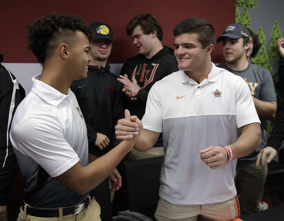 Photo - Corieon Lewis and Zach Middleton congratulate each other after signing to play football for Army and Oklahoma State University respectively during a signing day ceremony where he signed to play football at Oklahoma State at Bishop Kelley High School Wednesday, Dec. 18, 2019. MIKE SIMONS/Tulsa World