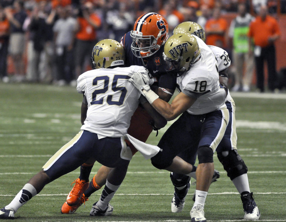 Photo -   Syracuse's Alec Lemon is wrapped up by Pittsburgh's Jason Handricks (25), Jarred Holly (18), and Manny Williams during the first quarter of an NCAA college football game in Syracuse, N.Y., Friday, Oct. 5, 2012. (AP Photo/Kevin Rivoli)