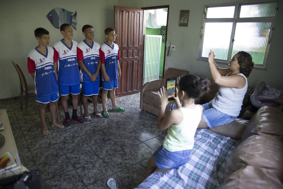 Photo - In this June 17, 2014 photo, Ana Lucia Rodrigues, right, takes a photo of her son Andre Rodrigues de Principe, known as Andrezinho to his neighbors, left, with his friends in their new soccer uniform, at their home in the Vidigal slum of Rio de Janeiro, Brazil. The road to soccer glory in Brazil is long and cruel. The humble favelas are breeding grounds for some of the world's top soccer talent. (AP Photo/Leo Correa)