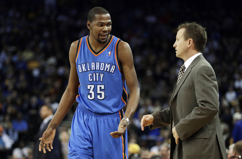 Photo - Oklahoma City Thunder's Kevin Durant (35) talks with head coach Scott Brooks during the first half of an NBA basketball game against the Golden State Warriors, Wednesday, Jan. 23, 2013, in Oakland, Calif. (AP Photo/Ben Margot)