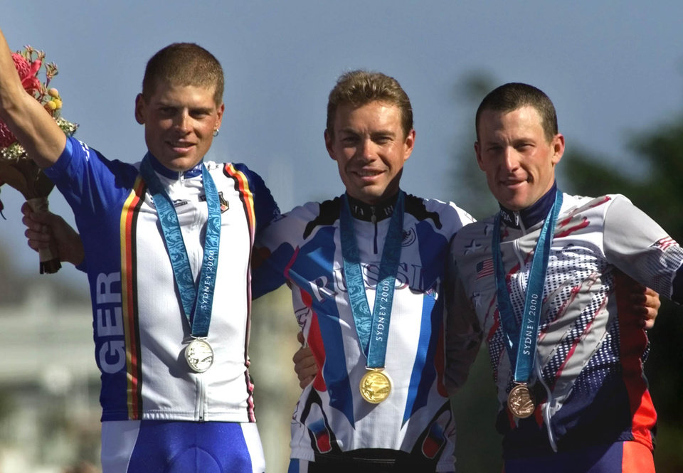 FILE - In this Saturday, Sept 30, 2000 file photo Russia's Viacheslav Ekimov, center, winner of the gold medal in the men's individual time trials, celebrates with Germany's silver medal winner Jan Ullrich, left, and U.S bronze medal winner Lance Armstrong at the cycling road course in Sydney, for the Summer Olympic Games. Officials familiar with the decision tell The Associated Press the IOC has stripped Lance Armstrong of his bronze medal from the 2000 Sydney Olympics because of his involvement in doping. Two officials say the IOC sent a letter to Armstrong on Wednesday night Jan. 16, 2013, asking him to return the medal. (AP Photo/Laurent Rebours, File)