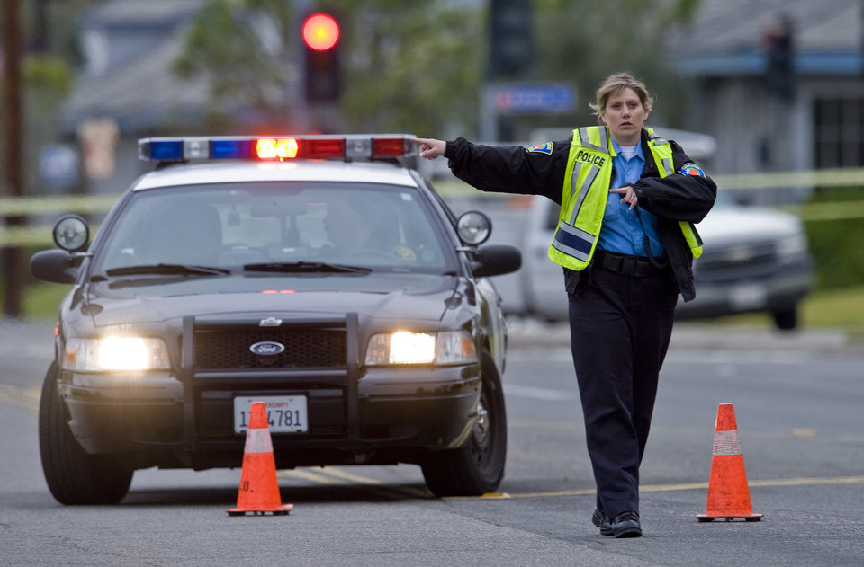 Photo - An Orange police officer directs traffic as an investigation of a shooting continues, Tuesday, Feb. 19, 2013 in Orange County, Calif. Police say a chaotic 25-minute shooting spree through Orange County left a trail of dead and injured victims before the shooter killed himself. Orange County sheriff's spokesman Jim Amormino say there are at least six crime scenes with three people, including the suspected gunman, dead and several others wounded. Tustin police Supervisor Dave Kanoti said the shootings started with an apparent carjacking just after 5 a.m. Tuesday in an unincorporated Ladera Ranch area of Orange County. (AP Photo/The Orange County Register, Mark Rightmire)   MAGS OUT; LOS ANGELES TIMES OUT