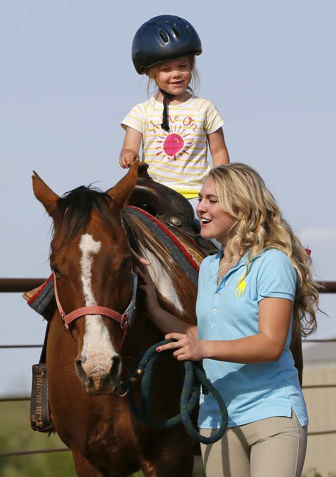 Photo - Molly Remondino, 17, leads a horse with rider Adyson Gray, 3, at the Peppers Ranch foster care community near Guthrie. Molly Remondino started a teen board to help with the equine therapy program and other activities at the ranch. Photo by Nate Billings, The Oklahoman   NATE BILLINGS
