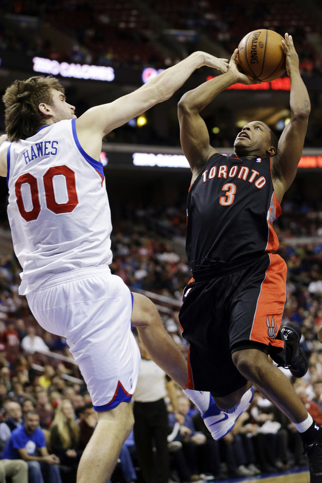 Toronto Raptors' Kyle Lowry (3) tries to get a shot past Philadelphia 76ers' Spencer Hawes in the first half of an NBA basketball game, Tuesday, Nov. 20, 2012, in Philadelphia. (AP Photo/Matt Slocum)