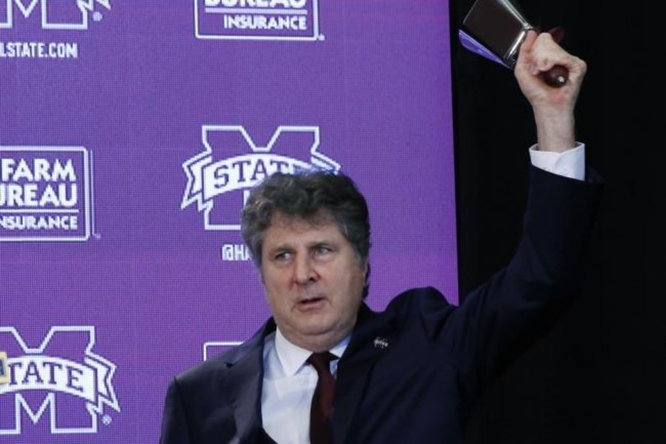 Photo -  New Mississippi State football coach Mike Leach rings the symbolic cowbell at a news conference Jan. 10 in Starkville, Miss. [AP Photo/Rogelio V. Solis]