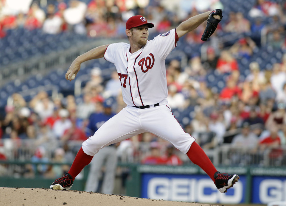 Photo - Washington Nationals starting pitcher Stephen Strasburg delivers the ball to the Texas Rangers during the first inning of a baseball game on Friday, May 30, 2014, in Washington. (AP Photo/Luis M. Alvarez)