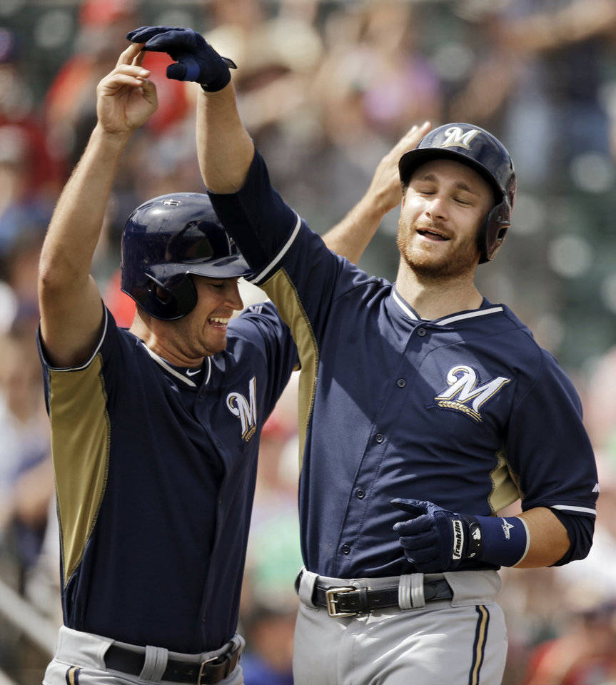 Photo - Milwaukee Brewers' Jonathan Lucroy, right, celebrates with Logan Schafer after Lucroy came around to score on a single and three-base error on Cincinnati Reds right fielder Jay Bruce in the second inning of a spring exhibition baseball game Sunday, March 23, 2014, in Goodyear, Ariz. Schafer scored ahead of Lucroy. (AP Photo/Mark Duncan)