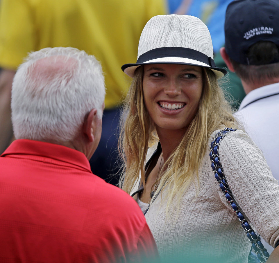 Photo - Tennis player Caroline Wozniacki speaks with Northern Ireland's Rory McIlroy's father Gerry McIlrory during the first round of the Masters golf tournament Thursday, April 11, 2013, in Augusta, Ga. (AP Photo/David J. Phillip)