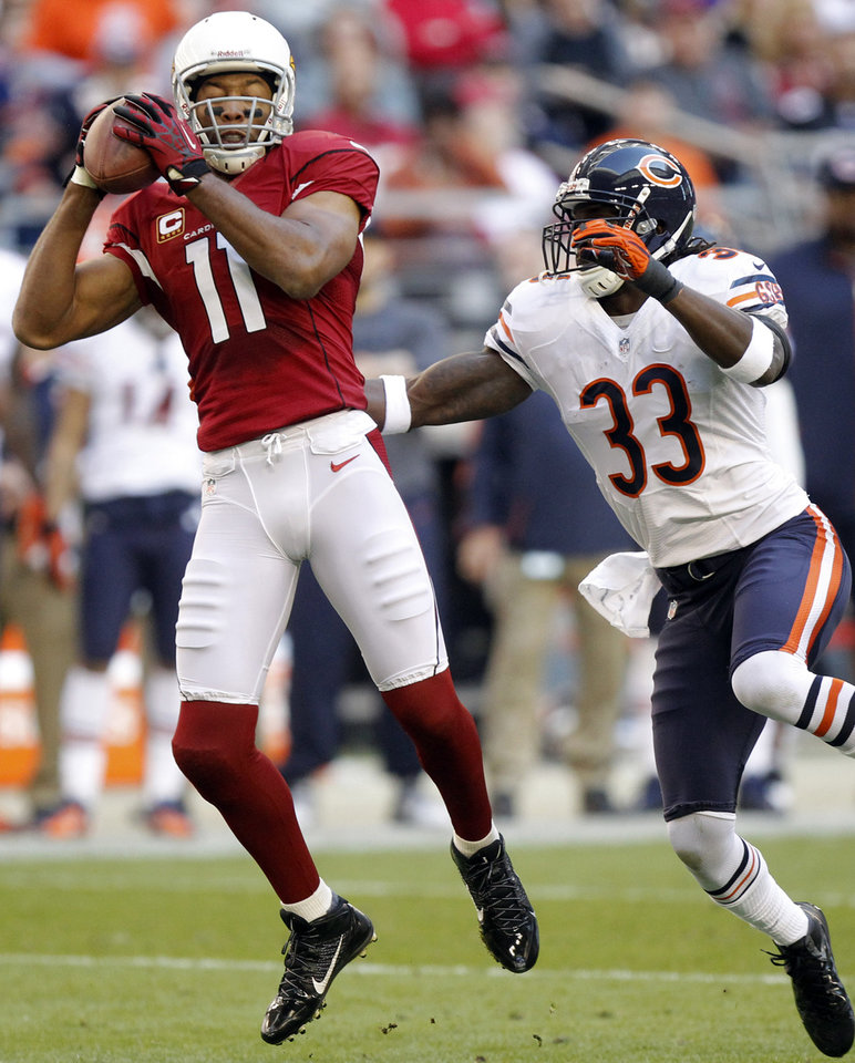 Photo - Arizona Cardinals wide receiver Larry Fitzgerald (11) pulls in a pass as Chicago Bears cornerback Charles Tillman (33) defends during the first half of an NFL football game, Sunday, Dec. 23, 2012, in Glendale, Ariz. (AP Photo/Paul Connors)