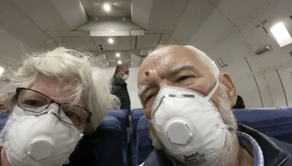 Photo -  In this image from a video taken on Monday, Feb. 17, 2020, Paul Molesky, right, and Cheryl Molesky, who evacuated off the quarantined cruise ship the Diamond Princess, film selfie video aboard a Kalitta Air plane bound for the U.S., at Haneda airport in Tokyo.(Cheryl and Paul Molesky via AP)