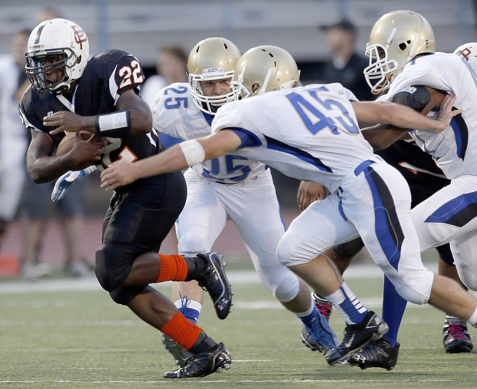 Photo - Putnam City's Denzel Dean gets by Choctaw's Kyle Lewallen (25) and Alex Thelin (45) during the high school football game between Putnam City and Choctaw at Putnam City High School in Oklahoma City, Thursday, Sept. 19, 2013. Photo by Sarah Phipps, The Oklahoman