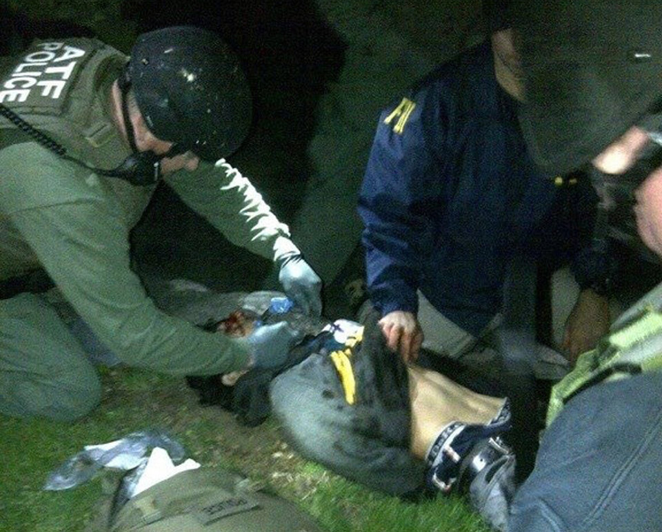 Photo - In this Friday, April 19, 2013 photo taken by the Massachusetts State Police, obtained by The Associated Press and authenticated by a member of the Bureau of Alcohol, Tobacco, Firearms and Explosives, ATF and FBI agents check suspect Dzhokhar Tsarnaev for explosives and also give him medical attention after he was apprehended in Watertown, Mass., at the end of a tense day that began with his older brother, Tamerlan, dying in a getaway attempt. Tsarnaev lay hospitalized in serious condition under heavy guard Saturday as investigators continue piecing together the who and why of the two brothers involved in the deadly Boston Marathon bombings. (AP Photo/Massachusetts State Police)