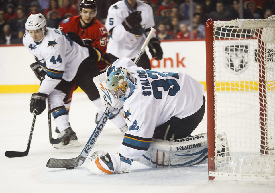 Photo - San Jose Sharks' goalie Alex Stalock, right, scoops up the puck as teammate Marc-Edouard Vlasic, left, keeps Calgary Flames' Kenny Agostino, center, away from the net during first period NHL hockey action in Calgary, Monday, March 24, 2014.(AP Photo/The Canadian Press, Jeff McIntosh)