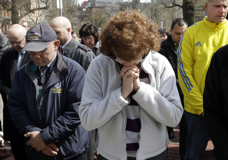 Photo - People pause for a moment of silence near the Statehouse in Boston at 2:50pm, Monday, April 22, 2013, exactly one week after the first bomb went off at the finish area of the Boston Marathon. (AP Photo/Elise Amendola)