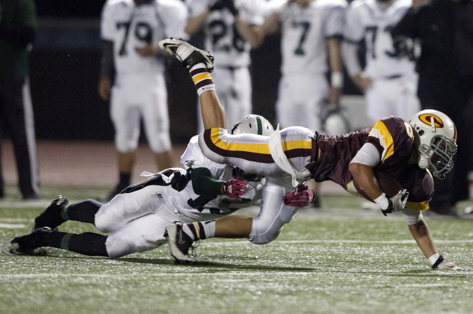 Clinton's Devon Mitchell is tripped up by Catoosa's Damontre Wallace during the high school Class 4A playoff game between Clinton and Catoosa at Putnam City High School.,  Friday, Nov. 25, 2011.  Photo by Sarah Phipps, The Oklahoman