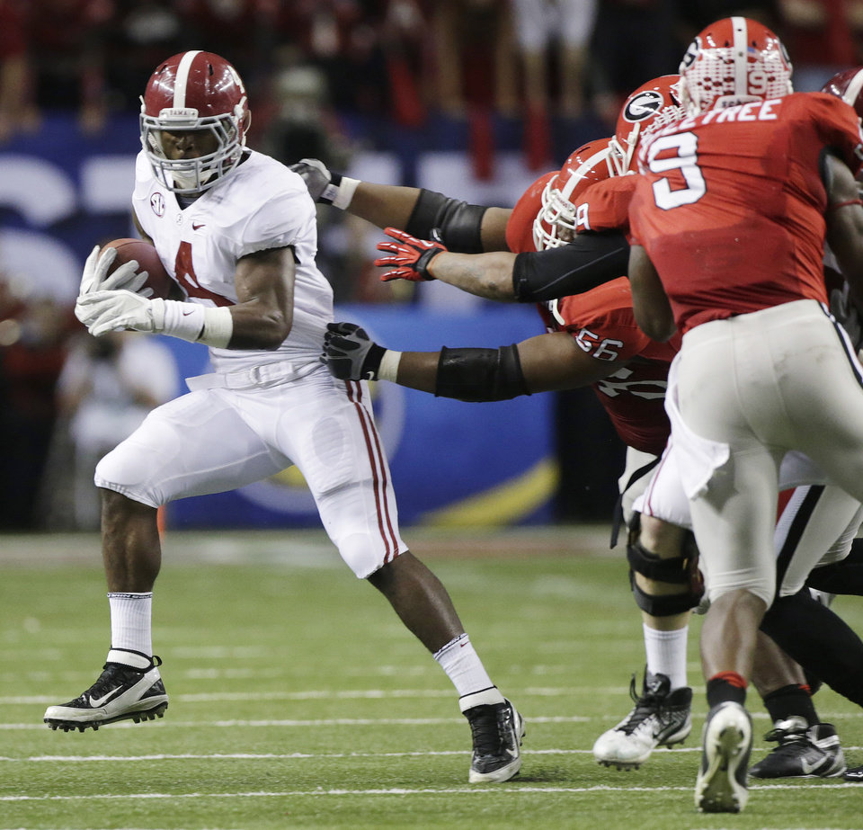 Photo - Alabama running back T.J. Yeldon (4) evades several Georgia defenders during the first half of the Southeastern Conference championship NCAA college football†game, Saturday, Dec. 1, 2012, in Atlanta. (AP Photo/Dave Martin)