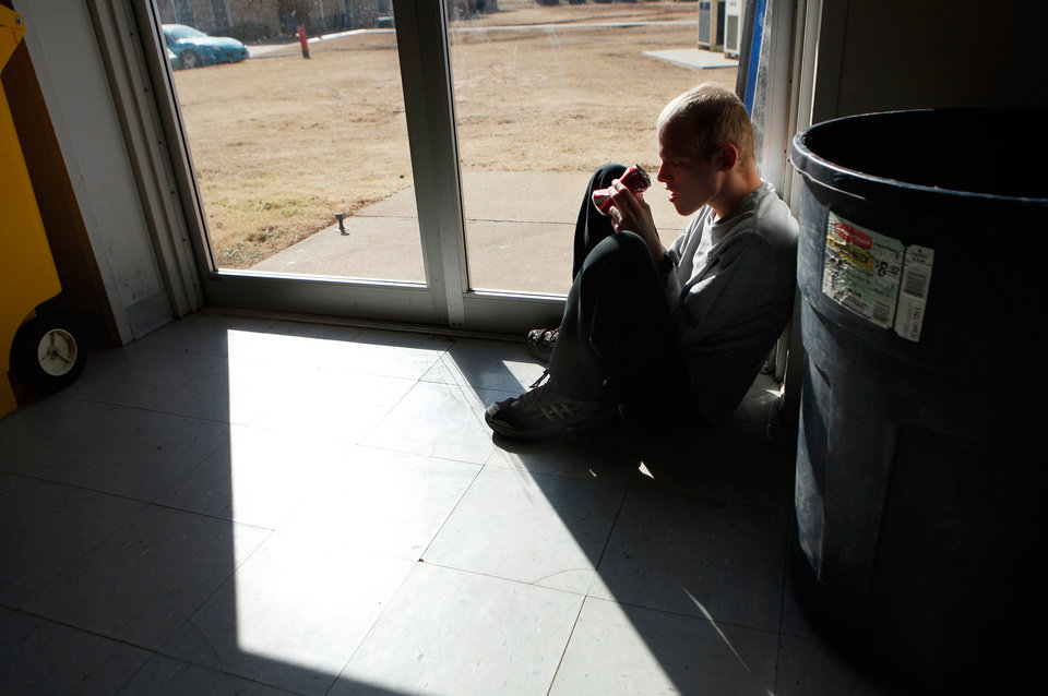 Photo - A resident sits in the sunlight next to a door in the gymnasium/multi-purpose room at the 54-bed  facility, Center of Family Love, a group home for mentally disabled people, in Okarche on Monday, Jan. 18, 2010.   Photo by Jim Beckel, The Oklahoman