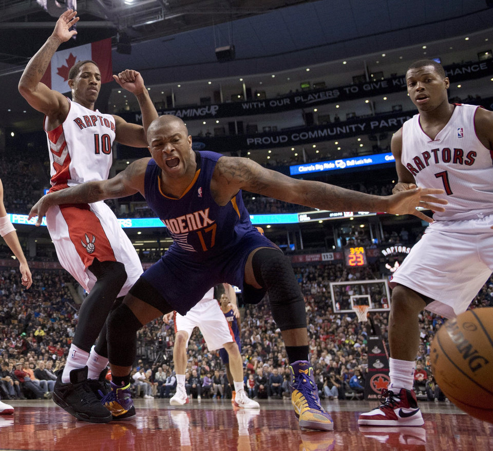 Photo - Phoenix Suns guard P.J.Tucker (17) lets out a yell after being fouled while rebounding against Toronto Raptors guards DeMar DeRozan (10) and Kyle Lowry (7) during the first half of an NBA basketball game in Toronto on Sunday, March 16, 2014. (AP Photo/The Canadian Press, Frank Gunn)