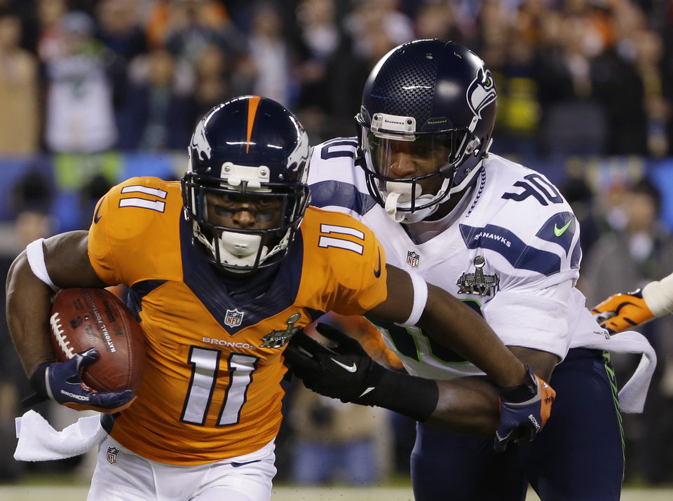 Photo - Denver Broncos' Trindon Holliday (11) runs from Seattle Seahawks' Derrick Coleman (40) during the first half of the NFL Super Bowl XLVIII football game Sunday, Feb. 2, 2014, in East Rutherford, N.J. (AP Photo/Matt Slocum)