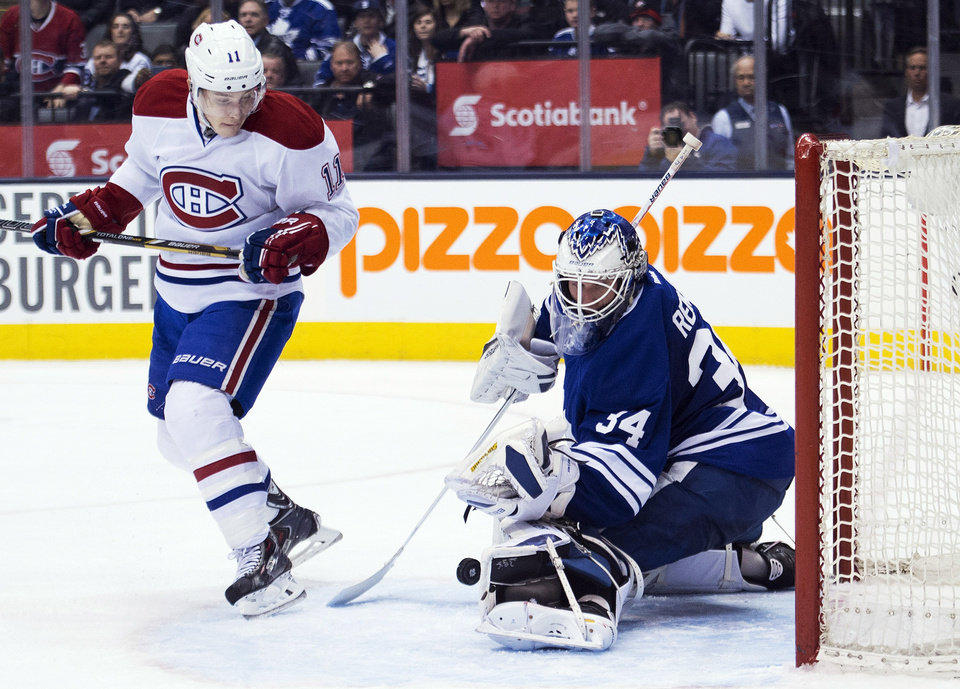 Photo - Toronto Maple goalie James Reimer, right, makes a save against Montreal Canadiens forward Brendan Gallagher, left, during third period of an NHL hockey game in Toronto on Saturday, March 22, 2014. (AP Photo/The Canadian Press, Nathan Denette)