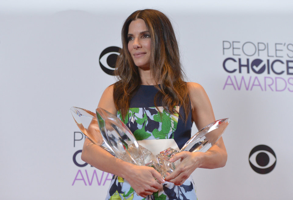 Photo - Sandra Bullock, winner of the Favorite Movie Actress, Favorite Dramatic Movie Actress and Favorite Comedic Movie Actress poses in the press room at the 40th annual People's Choice Awards at Nokia Theatre L.A. Live on Wednesday, Jan. 8, 2014, in Los Angeles. (Photo by John Shearer/Invision/AP)