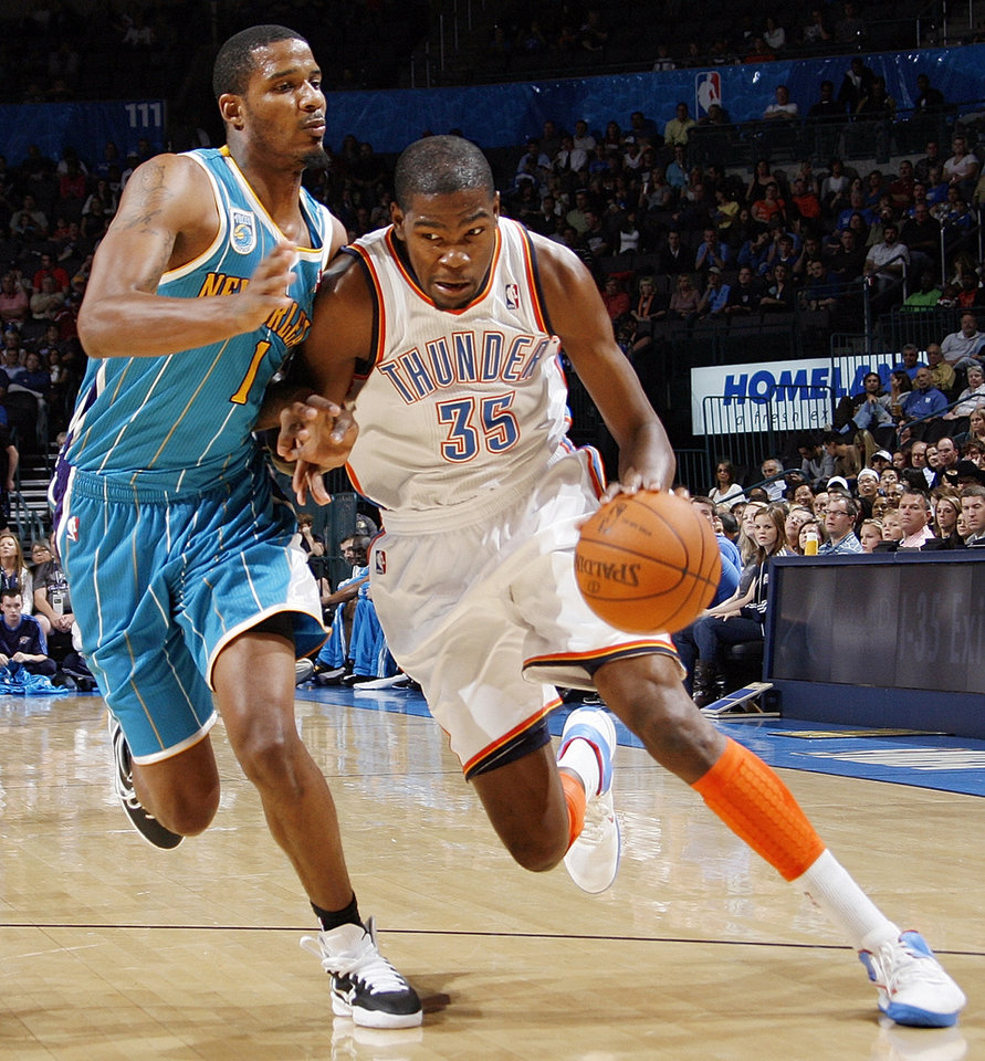 Photo - Oklahoma City's Kevin Durant (35) drives the ball past Trevor Ariza (1) of New Orleans during the preseason NBA basketball game between the New Orleans Hornets and the Oklahoma City Thunder at the Ford Center in Oklahoma City, Thursday, October 21, 2010. Photo by Nate Billings, The Oklahoman