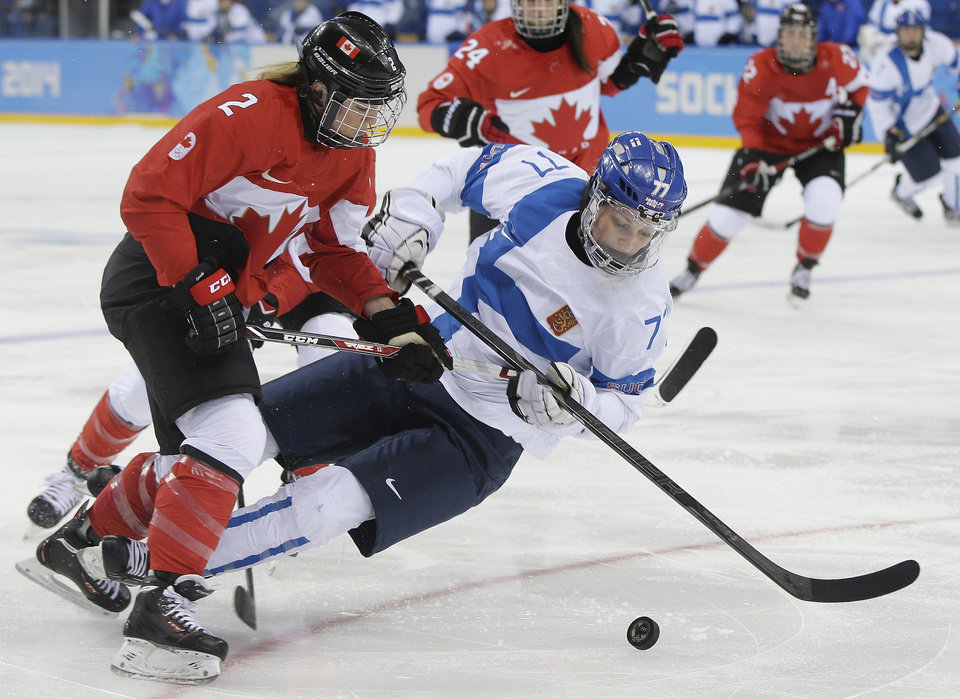 Photo - Susanna Tapani of Finland falls as she challenges Meghan Agosta-Marciano of Canada for control of the puck during the third period of the 2014 Winter Olympics women's ice hockey game at Shayba Arena, Monday, Feb. 10, 2014, in Sochi, Russia. (AP Photo/Matt Slocum)