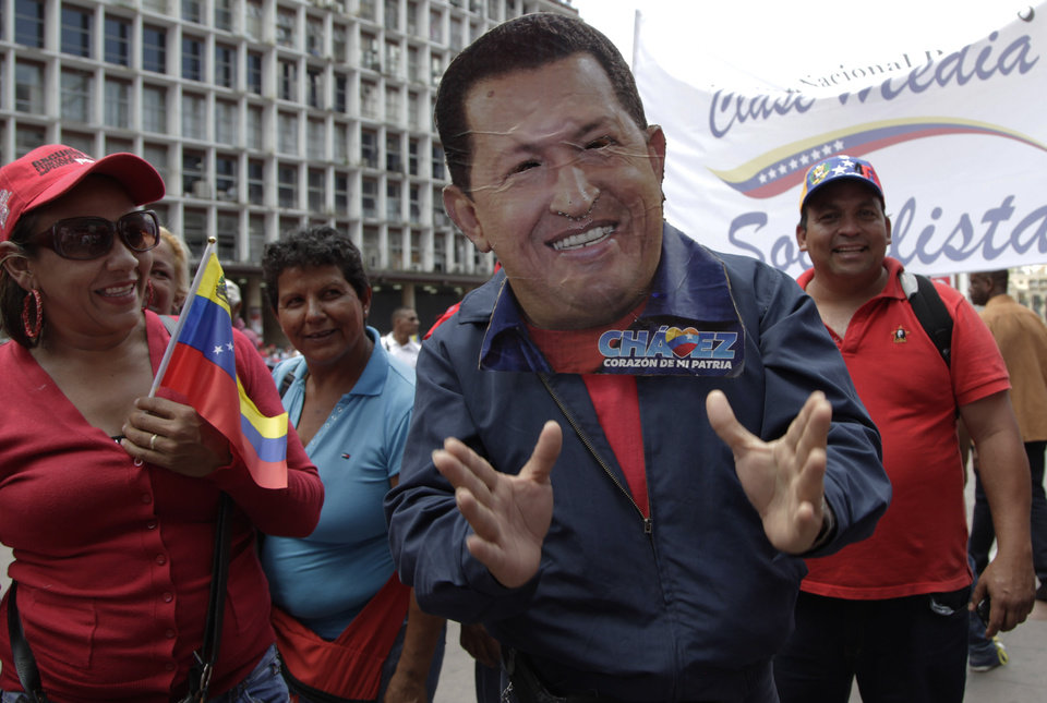 Photo - A man wearing a handcrafted mask depicting the face of Venezuela's President Hugo Chavez attends an event commemorating the violent street protests of 1989 known as the