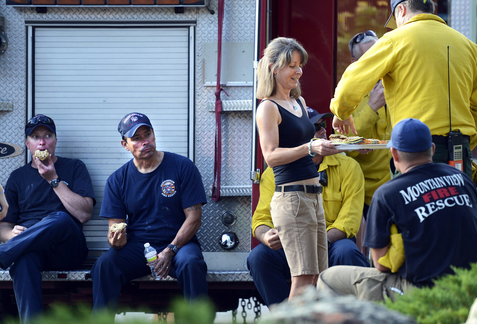 Photo -   Karen Jones hands out homemade cookies to firefighters at the intersection of Cragmoor Road and View Point Drive in Boulder, Colo., on Wednesday, June 27, 2012. A Boulder fire and police spokeswoman said a wildfire burning west of Boulder is now within a mile and a half of the city, and fire managers are competing for resources as three major wildfires continue to burn in Colorado. (AP Photo/The Daily Camera, Jeremy Papasso) NO SALES
