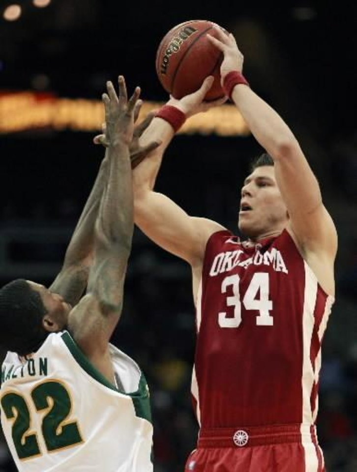 Photo - Oklahoma guard Cade Davis (34) shoots over Baylor guard A.J. Walton (22) during the second half of an NCAA college basketball game in the first round of the Big 12 men's tournament in Kansas City, Mo., Wednesday, March 9, 2011. Oklahoma defeated Baylor 84-67. (AP Photo/Orlin Wagner) ORG XMIT: MOOW105