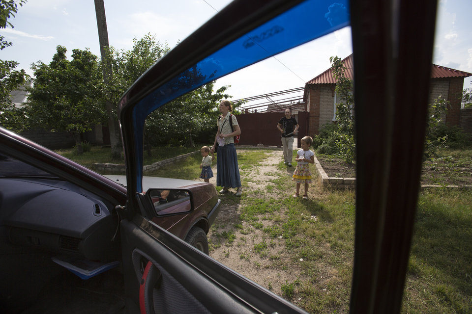 Photo - Olga Mikhailova, second left, and  her husband Vladimir Mikhailov, second right, prepare their children to leave their home in Slovyansk, Ukraine, Wednesday, May 28, 2014.  In Slovyansk, a city 90 kilometers (55 miles) north of Donetsk which has seen repeated clashes over the past few weeks, with residential areas comming under mortar shelling Wednesday from government forces. A school was badly damaged and other buildings were hit, according to residents, Wednesday who told The Associated Press that several people were wounded.(AP Photo/Alexander Zemlianichenko)