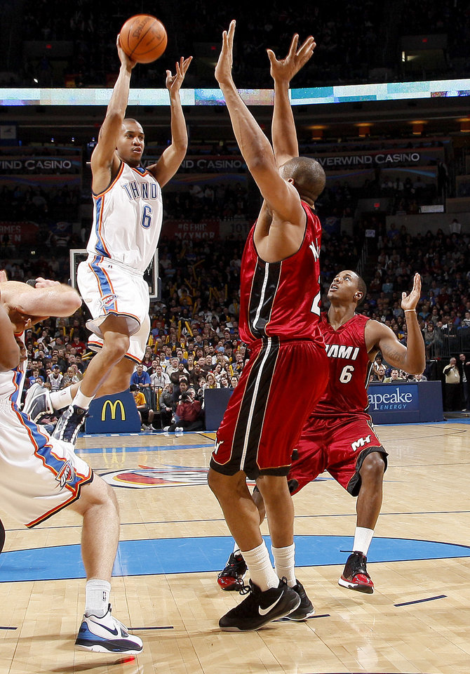 Photo - Oklahoma City's Eric Maynor passes the ball over Miami's Jamaal Magloire and Mario Chalmers, right, during the NBA basketball game between the Oklahoma City Thunder and the Miami Heat at the Ford Center in Oklahoma City, Saturday, January 16, 2010. Photo by Bryan Terry, The Oklahoman