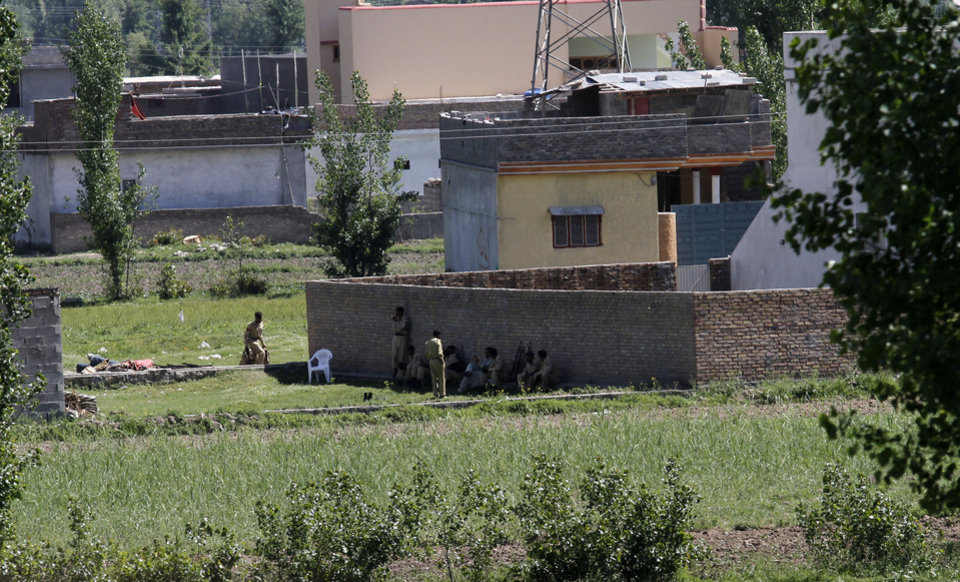 Photo - Pakistan army soldiers rest near the house where it is  believed al-Qaida leader Osama bin Laden lived in Abbottabad, Pakistan on Monday, May 2, 2011. Bin Laden, the glowering mastermind behind the Sept. 11, 2001, terror attacks that killed thousands of people, was slain in his hideout in Pakistan early Monday in a firefight with U.S. forces, ending a manhunt that spanned a frustrating decade. (AP Photo/Anjum Naveed)