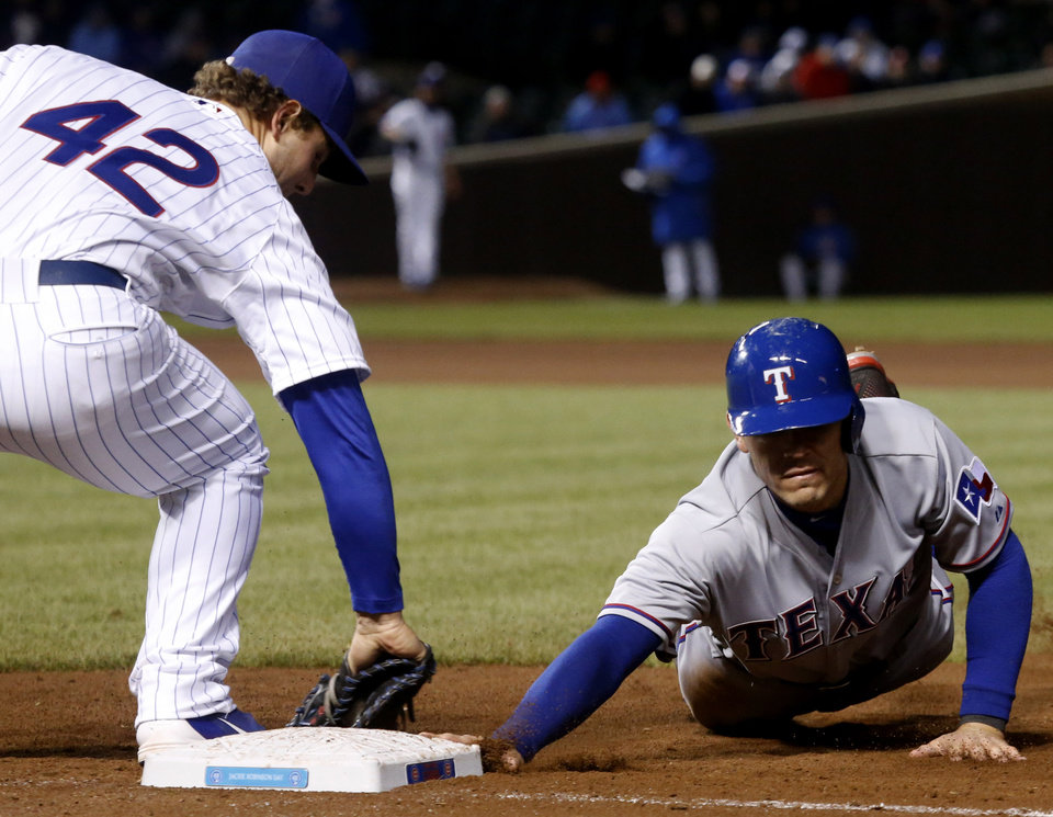 Texas Rangers' Ian Kinsler, right, is save at first after a pick off attempt by Chicago Cubs relief pitcher Shawn Camp to first baseman Anthony Rizzo, during the eighth inning of a interleague baseball game, Tuesday, April 16 2013, in Chicago. (AP Photo/Charles Rex Arbogast)