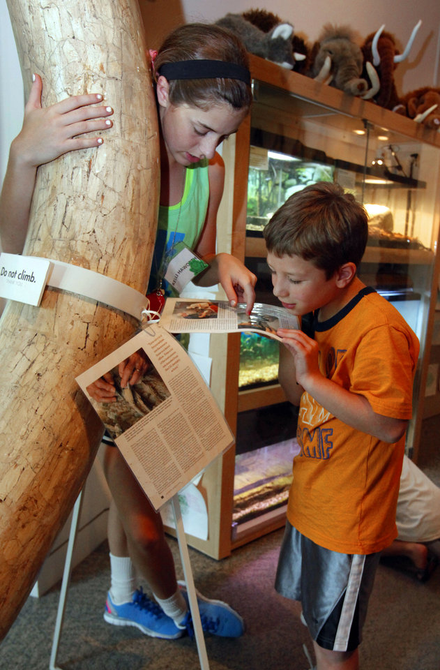 Photo - Volunteer Kelli Haworth, left, helps Oklahomans Without Limits camper Avery Carrington, 9, of Tulsa, understand an exhibit Wednesday at the Sam Noble Oklahoma Museum of Natural History. PHOTO BY STEVE SISNEY, THE OKLAHOMAN