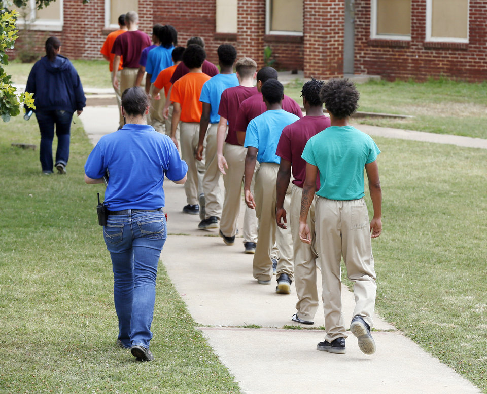 Photo -  Residents are escorted on grounds of the Central Oklahoma Juvenile Center in Tecumseh. [Photo by Nate Billings, The Oklahoman]
