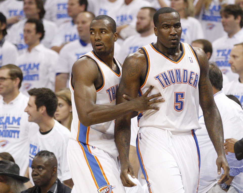 Photo -   Oklahoma City Thunder forward Serge Ibaka , left, pushes teammate Kendrick Perkins, right, away from an altercation in the first half of Game 2 in the first round of the NBA basketball playoffs against the Dallas Mavericks in Oklahoma City, Monday, April 30, 2012. (AP Photo/Sue Ogrocki)