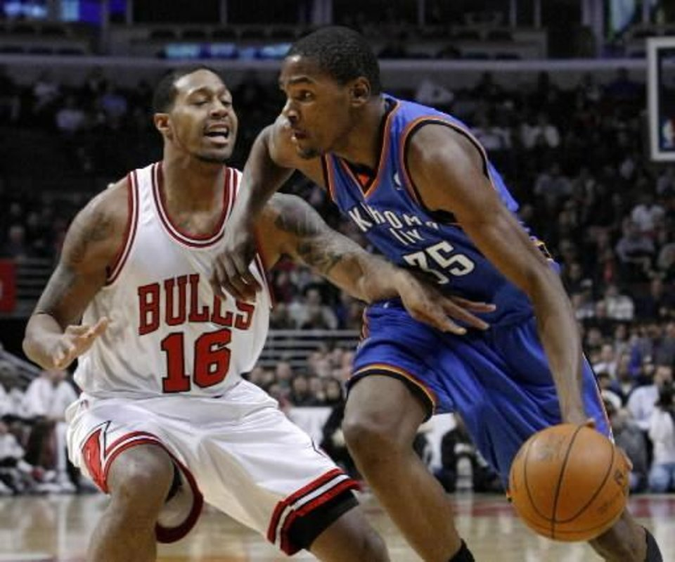 Oklahoma City  Thunder forward Kevin Durant, right, drives on Chicago  Bulls guard James Johnson during the first half of an NBA basketball game Monday, Jan. 4, 2010, in Chicago. (AP Photo/Charles Rex Arbogast)