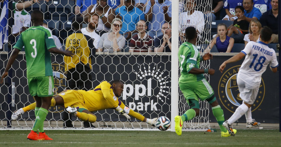 Photo - Nigeria goalkeeper Vincent Enyeama, center, dives to block a shot by Greece midfielder Ioannis Fetfatzidis, right, as defender Elderson Echiéjilé, left, and midfielder Ogenyi Onazi look on during the first half of an an international friendly soccer match, Tuesday, June 3, 2014, in Chester, Pa. (AP Photo/Matt Slocum)