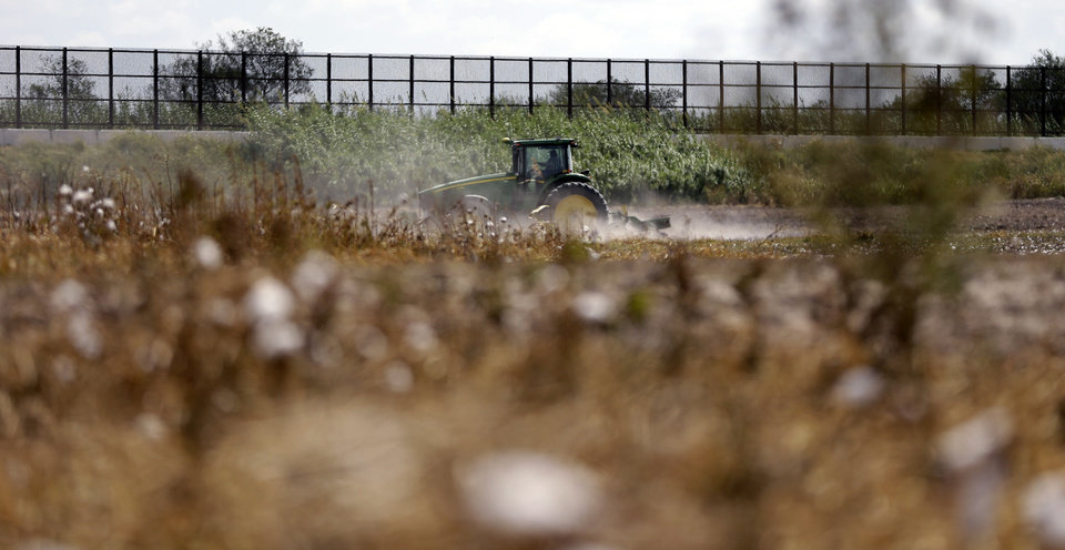 In this Sept. 6, 2012, photo, a tractor is used to farm in cotton field along the U.S.-Mexico border fence that passes through the property in Brownsville, Texas. Since 2008, hundreds of landowners on the border have sought fair prices for property that was condemned to make way for the fence, but many of them received initial offers that were far below market value. (AP Photo/Eric Gay)