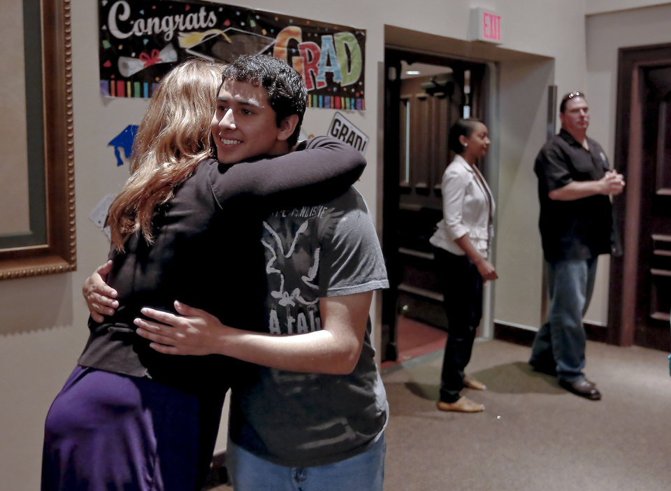 Photo - Mallory Cantrell, director of the Supporting Kids in Independent Living (SKIL)  program, hugs new graduate Roy Guierrez after he walked across the stage during the SKIL graduation. Gutierrez will attend hte University of Oklahoma on a ballet scholarship. PHOTO BY CHRIS LANDSBERGER, THE OKLAHOMAN.  CHRIS LANDSBERGER