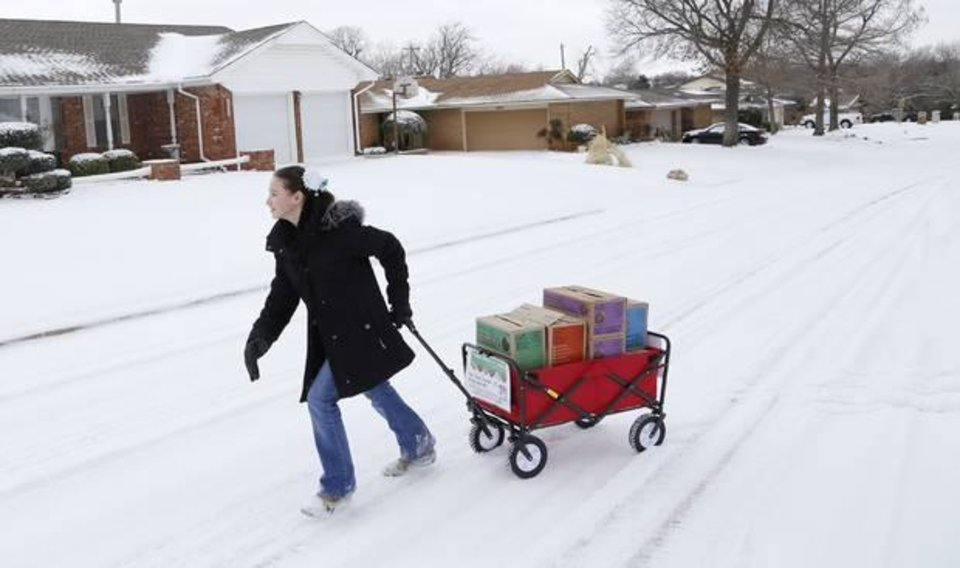 Photo -  Girl Scout Katie Francis pulls her wagon full of boxes of cookies in the snow through a neighborhood in Warr Acres sellling cookies Thursday, February 6, 2014. Photo by Doug Hoke, The Oklahoman Archive