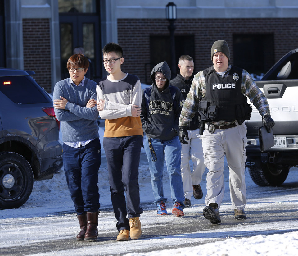 Photo - Police evacuate students from the Electrical Engineering building after shots were fired on Tuesday, Jan. 21, 2014, on the campus of Purdue University in West Lafayette, Ind.  Officials at Purdue University say one person has been killed in a shooting at the campus classroom building. Purdue Provost Tim Sands says he didn't immediately know the identity of the person killed or the person's connection to the university. Campus police chief John Cox says the suspect is in custody after surrendering outside the Electrical Engineering Building following the shooting.   (AP Photo/Journal & Courier, John Terhune)   MANDATORY CREDIT