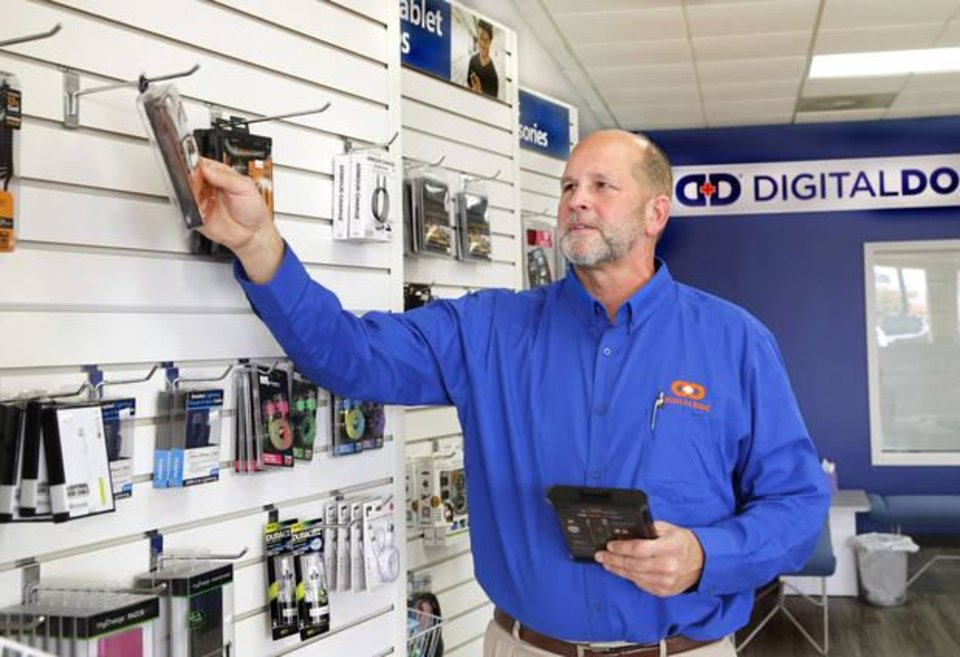 Photo -  Reid Nuttall, owner of a Digital Doc franchise, poses in his new store on N May Avenue. [PHOTO BY JIM BECKEL, THE OKLAHOMAN]