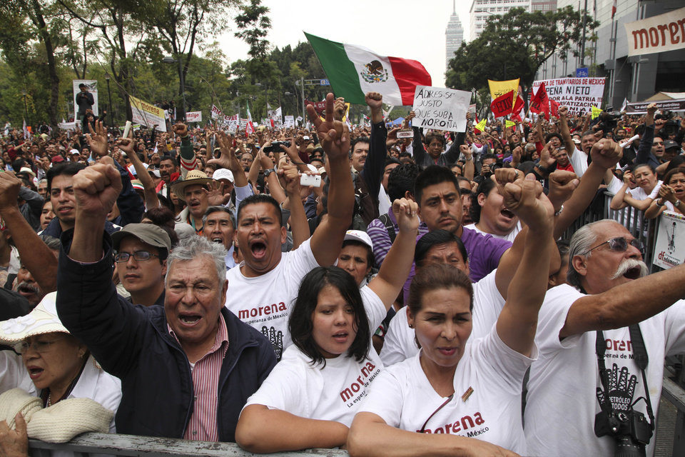 Photo - Supporters of former presidential candidate Andres Manuel Lopez Obrador cheer as they listen to Lopez Obrador during an act to protest against the governments proposed energy reforms that would allow private companies to explore the country's oil and gas reserves, in Mexico City, Sunday Sept. 8, 2013. The proposed reform requires constitutional changes that strike at the heart of one of Mexico's proudest moments: President Lazaro Cardenas' nationalization of the oil company in 1938. (AP Photo/Marco Ugarte)